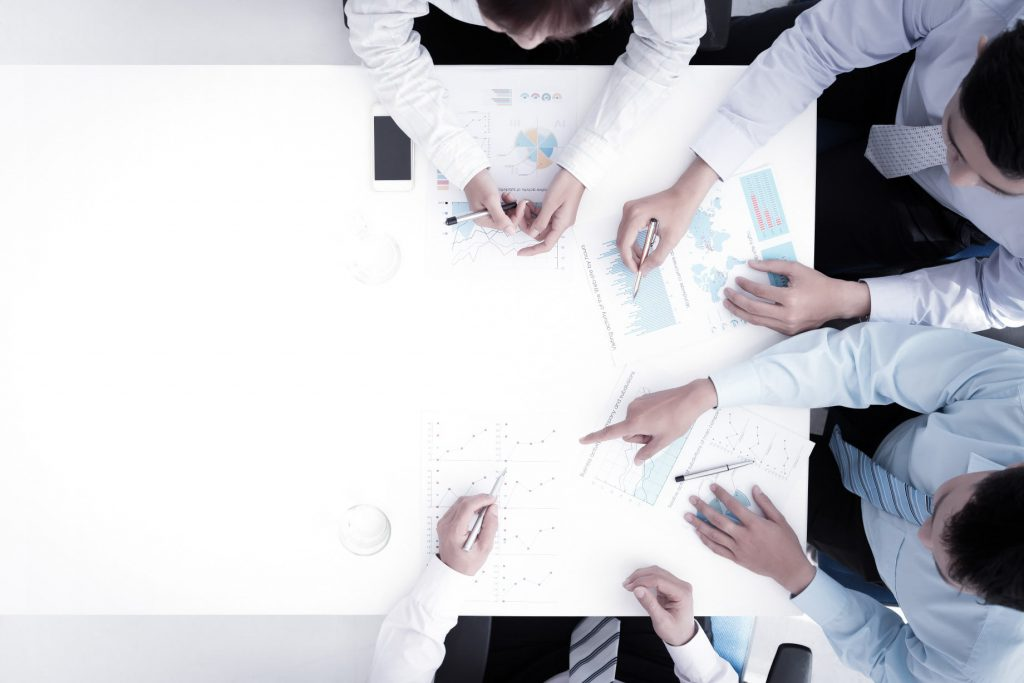 デスクを囲んでミーティングする四人